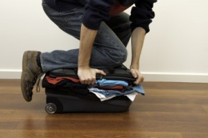 PACKING_LUGGAGE_HOLDING_SUITCASE_CLOSED